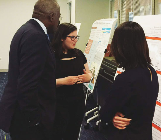 Chancelor Jones discusses poster with 2 students