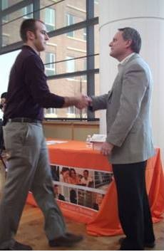 John Foley, second-year MBA, shakes Dean Lanesskog's hand as he accepts his nomination award.