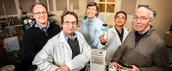 four men and a woman standing in a lab