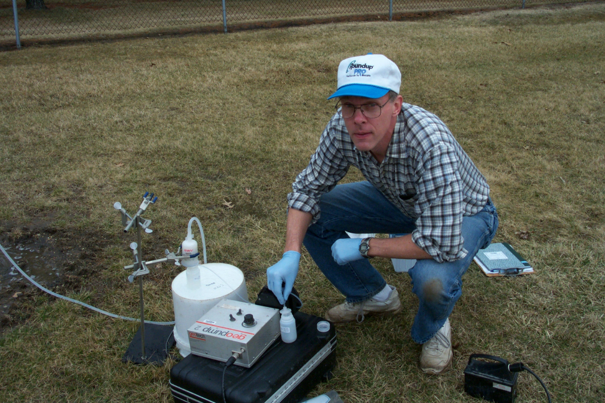 Tom Holm crouches next to water sampling equipment, circa 2002