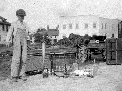 boy in overalls and a cap stands near water testing equipment, a horse drawn wagon is nearby