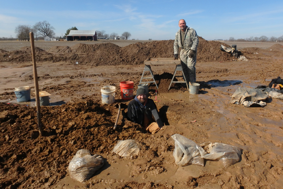 Patrick Durst's head and chest are visible as he stands in an excavation, with Steven Boles standing six feet behind him
