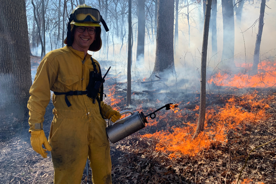 Michael Aiuvalasit participating in a prescribed burn with the Champaign County Forest Preserve.