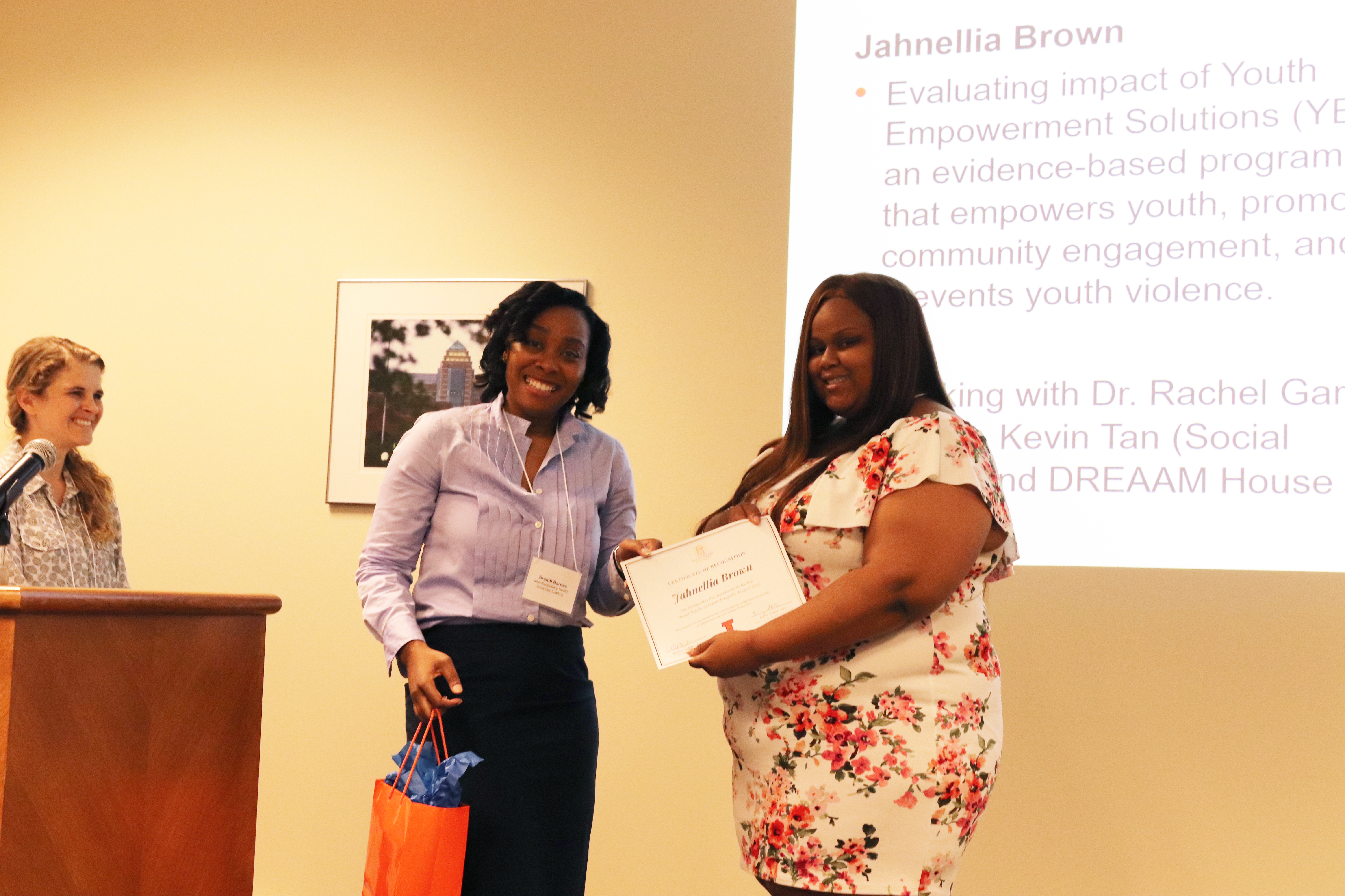 Jahnellia receiving her certificate from Health Equity Scholars program manager Brandi Barnes