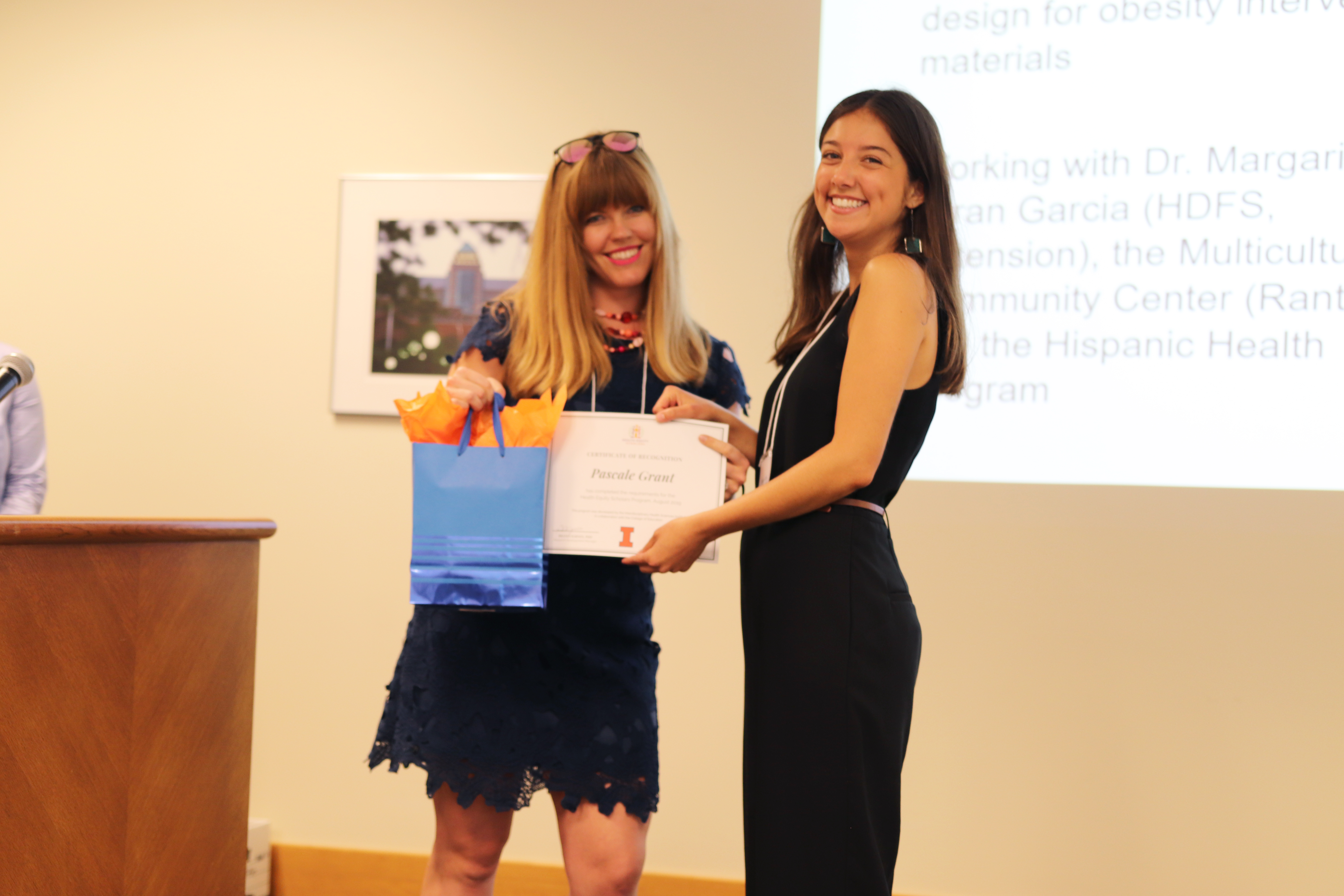 Pascale receiving her certificate from Health Equity Scholars program manager Kelsey Hassevoort