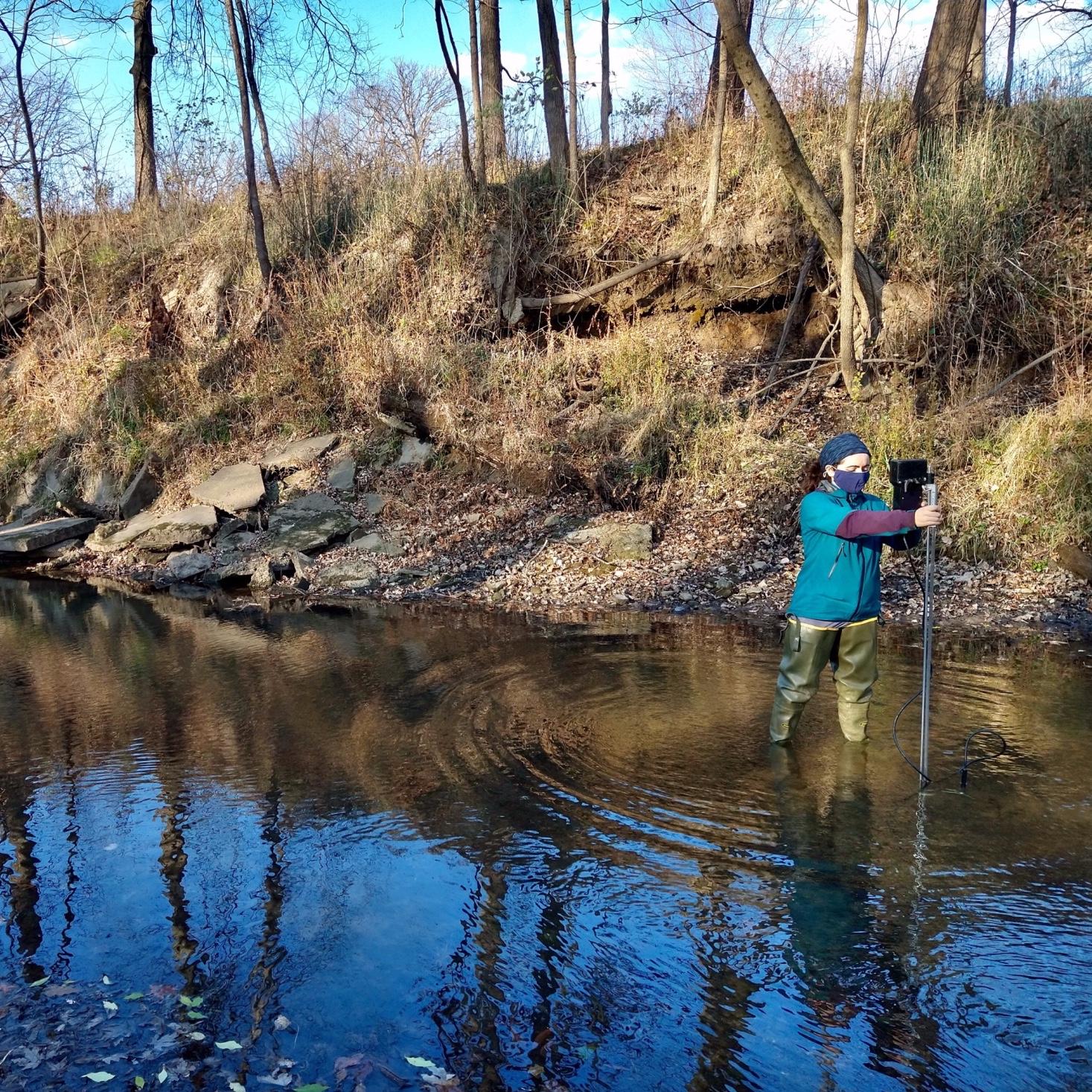 Margaret Golden setting up equipment in a river.
