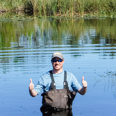 John Gatto standing in water in waders