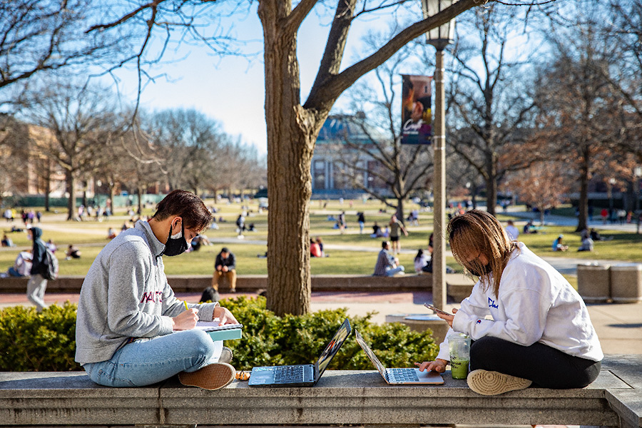 Students on studying on computers on the Quad with face masks on during COVID