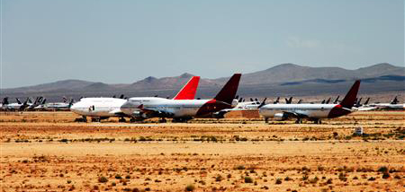 Three airplanes sit in the desert, with many more grounded planes in the distance behind them.