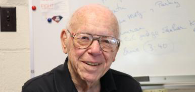 Harry H. Hilton, an elderly white man with a bald head and glasses, smiles at the camera. He is in front of a whiteboard with writing on it.