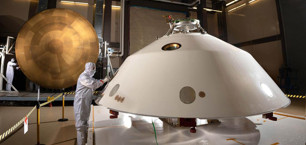 It displays the photo of the heat shield (left) and back shell (right) comprise the aeroshell for NASA's Mars 2020 mission.