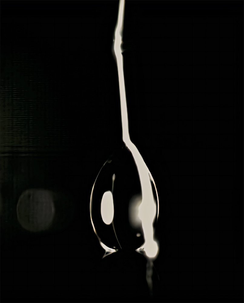 A drop of water appears black with a white line on one side against a black background.