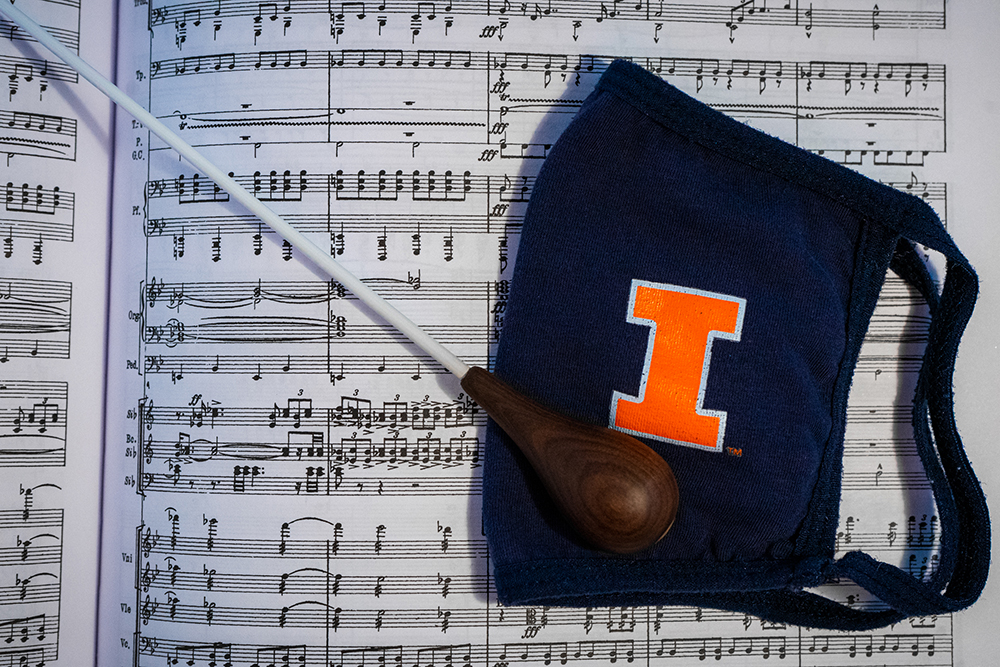 A baton and dark blue facemask with an orange I laid on top of a musical score.